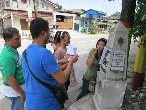 "Several people are taking down notes beside a small street-side historical marker bearing the title ""Death March, KM 93""."
