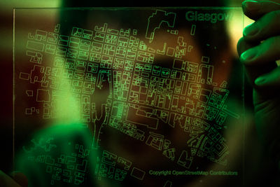 a transparent laser-etched acrylic map of OpenStreetMap buildings in central Glasgow with a green glow and a person behind