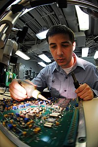 US Navy 090414-N-9928E-128 Electronics Technician 3rd Class Alex Head, from Carmel, Ind., repairs components on a circuit board in the micro-miniature repair shop aboard the aircraft carrier USS John C. Stennis (CVN 74).jpg