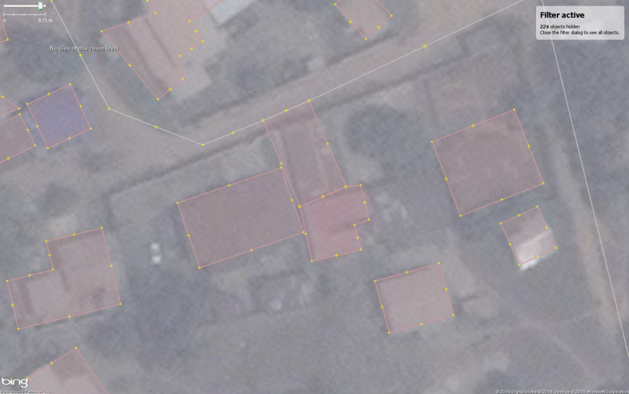Typical buildings in West African city with a common mapping mistake, shared nodes with roads and other buildings.