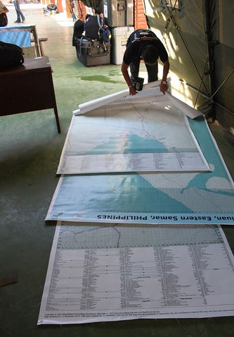 three large poster maps of Tacloban, Guiuan and Ormoc on the floor for post-typhoon aid