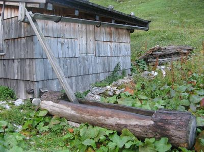 wooden trough fed by water from the rain gutter of a hut